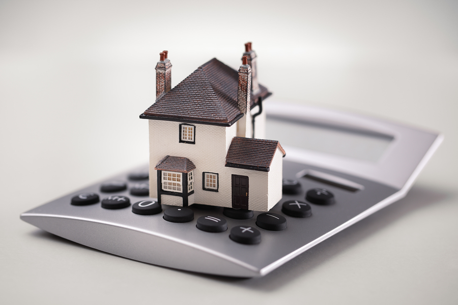 House resting on calculator concept for mortgage calculator, hom
